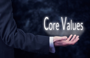 The arm of a businessman holding the words Core Values.